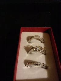 three silver-colored rings with clear gemstones and red box