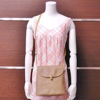 women's pink and white sleeveless dress and brown leather crossbody bag