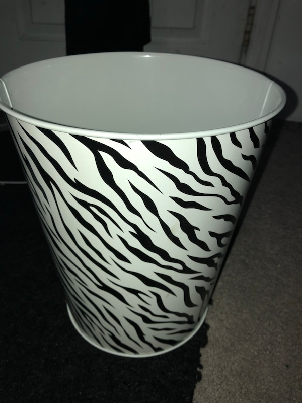 White and black zebra print trash bin