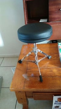 round black leather padded seat with grey stainless steel base