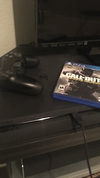black Sony PS4 console with controller and game case