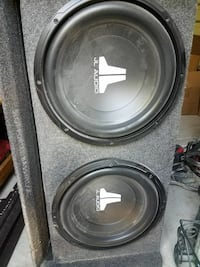 two black JL Audion subwoofers with enclosure