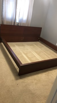 Brown wooden bed frame with white mattress