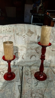 two gray pillar candles on red translucent glass candle holders