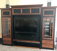 black flat screen TV with brown wooden entertainment center Leesburg