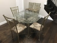 Round glass top table with six chairs dining set. Also selling 2 matching counter height chairs included in price 500 km