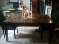 Marble dining room table with two black leather chairs
