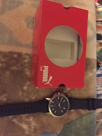 round silver-colored Puma analog watch with black band and box