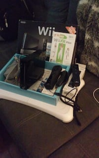 black Xbox 360 console with controller and game cases TORONTO