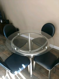 round clear glass top table with four chairs