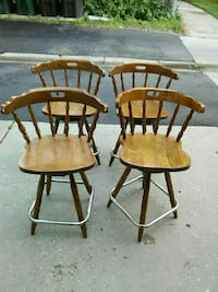 four brown wooden dining chairs