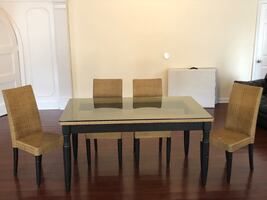 Glass kitchen  table with 4 wicker chairs.