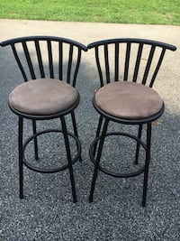 two black metal framed brown padded chairs