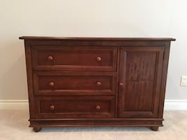 Brown wooden three-drawer chest with single-door cabinet