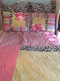 Yellow, pink, black, and white floral bedspread with pillows full/queen. Bought from Neimans Gainesville, 20155