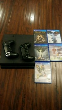 black Sony PS4 console with controller and game cases Montréal, H2P