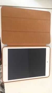 white iPad with brown leather flip case 541 km
