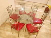 round clear glass-top table with four chairs  Mumbai, 400102