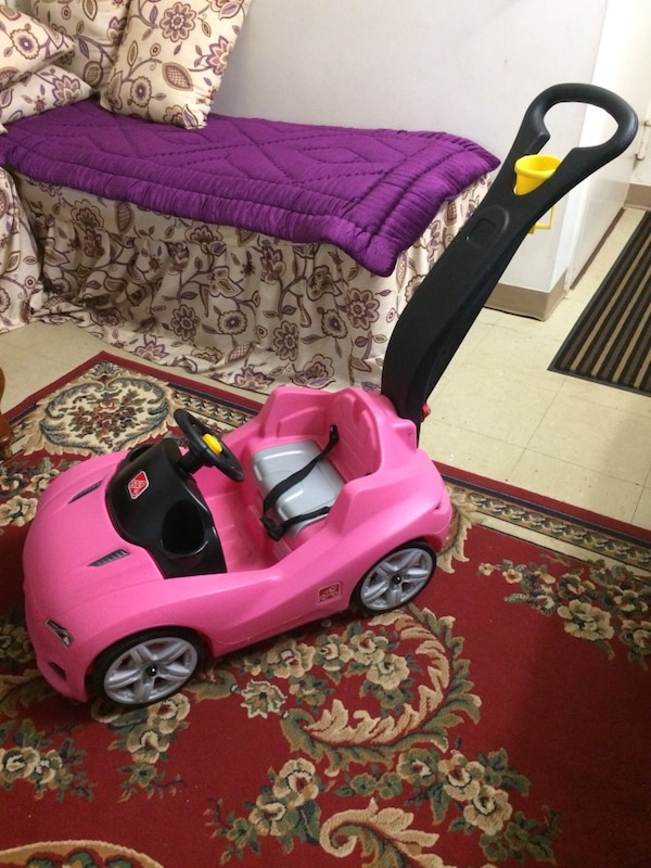 toddler's pink and black ride on toy car