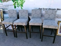 four brown wooden framed gray padded chairs