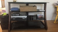 brown wood-framed black glass television stand