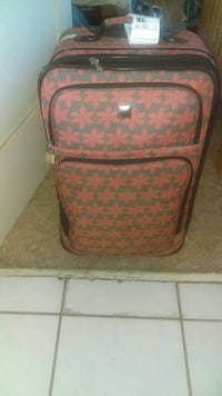 gray and red floral luggage bag