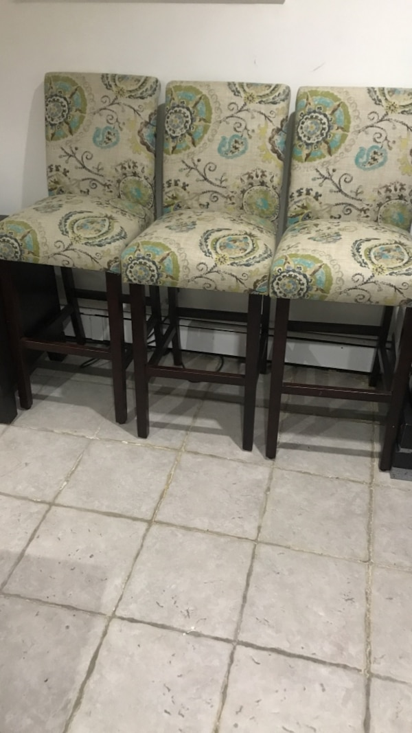 Three brown wooden framed floral padded chairs