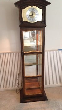 Brown curio cabinet with clock