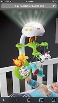 White and green fisher-price crib mobile