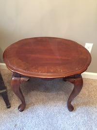 Round brown wooden coffee table with cabriole leg