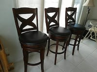 three black leather padded brown wooden barstools