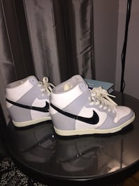 white-and-gray Nike mid top sneakers