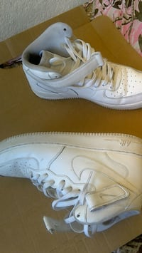 pair of white Nike Air Force 1 high shoes