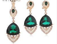 gold-colored pendant with green and white gemstones and pair of earrings