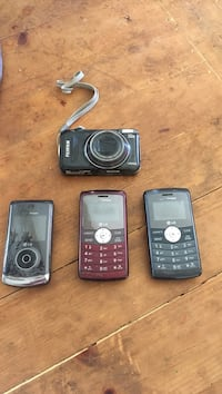 black Fujifilm point-and-shoot camera, black LG flip phone, and two red and black LG candybar phones