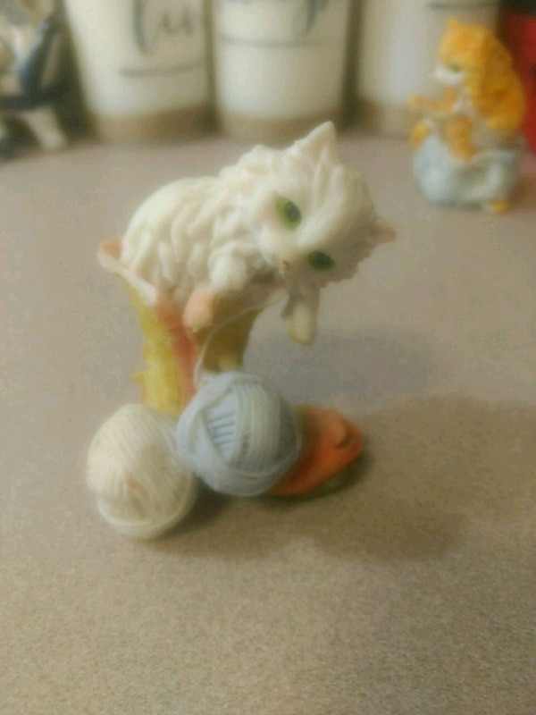 Cat playing with balls of yarn figurine