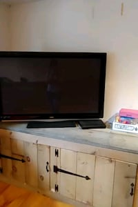 flat screen television with brown wooden TV hutch Londonderry, 03053
