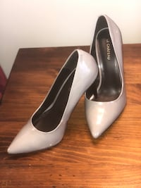 pair of white leather pointed-toe heeled shoes