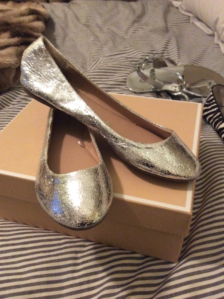 women's pair of gray suede flats on box