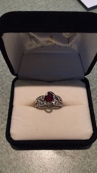 Silver and red gemstone ring in box