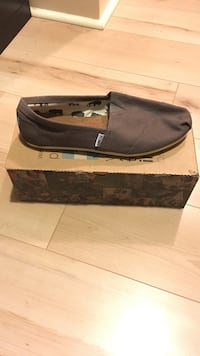 unpaired brown Tom's slip-on shoe with box