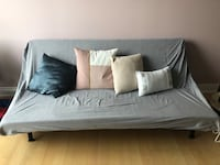 Gray fabric sofa bed with throw pillows
