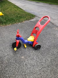 Tricycle with push handle and foot pegs.