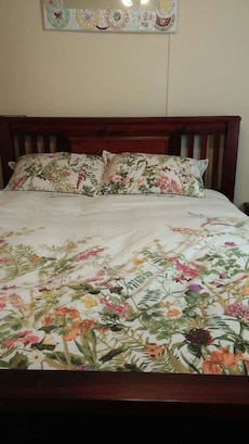 brown wooden bed frame with white floral blanket and throw pillows