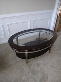 round black wooden framed glass top coffee table