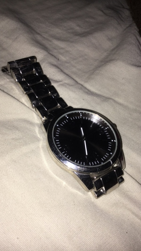 Round black analog watch with silver link bracelet