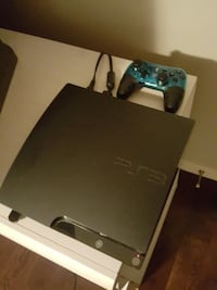black PS3 slim console with controller and games