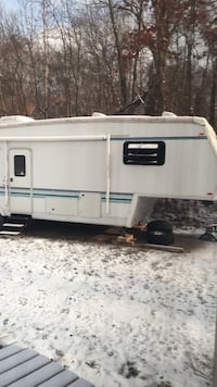 white and blue travel trailer