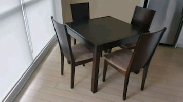 rectangular black wooden table with four chairs di