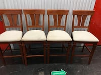 Six white padded chairs with brown wooden frames 45 km